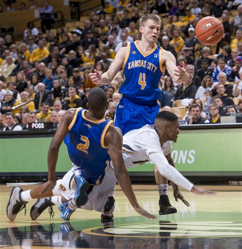 Missouri's Keith Shamburger, right, is fouled as he collides with UMKC's Deshon Taylor, left, and Mason Wedel, top, during the first half in an NCAA college basketball game Friday, Nov. 14, 2014, in Columbia, Mo. (AP Photo/L.G. Patterson)